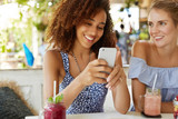Photo of two lesbians use modern electronic gadget together, enjoy wireless internet connection at cafe. African American female holds mobile phone, shows something online to European friend - 193075982
