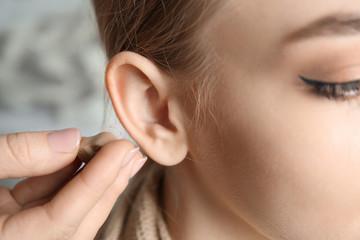 Doctor putting hearing aid in woman's ear, closeup