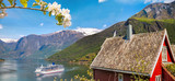 Red cottage against cruise ship in fjord, Flam, Norway - 193086335