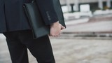 Man in black suit walks with a folder - 193087199