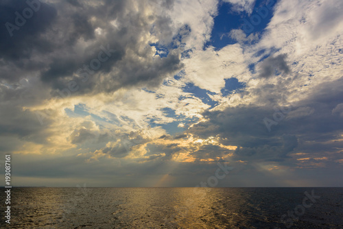Foto op Plexiglas Beige The rays of the sun, making their way through thunderclouds over the ocean