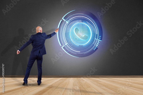 Businessman in front of a wall with a Shinny technologic phone button - 3d render