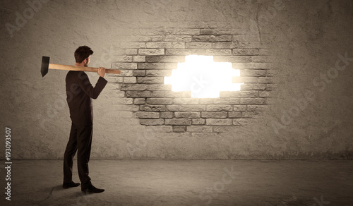 Business man hitting brick wall with hammer and opening a hole - 193093507