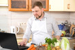 Quadro A man prepares food on a prescription from the Internet. An adult 40 year old man leads a culinary on-line blog about healthy eating.