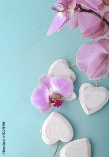 pink orchid and wooden white heart on blue background