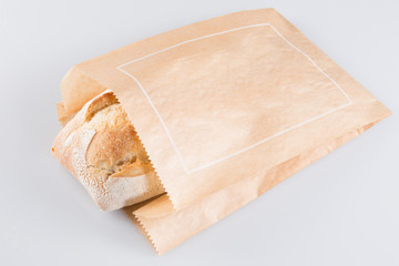 Fresh baguette in paper bag on white background