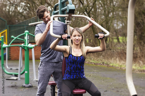 Beautiful couple doing exercise on training machine outdoor. Man watching how woman doing push up