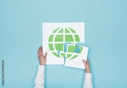 Foto Murales Woman completing a puzzle with a globe