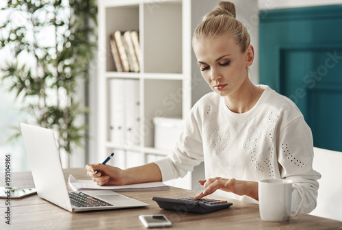 Foto Murales Concentrated woman budgeting at office