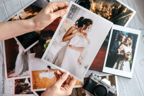 Fototapeta Printed wedding photos with the bride and groom, a vintage black camera and woman hands with photo