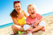 cheerful modern mother and child sitting on beach