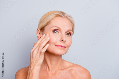 Leinwandbild Motiv Pretty, charming, attractive woman touching, enjoying her perfect face skin, holding fingers on cheek, pimple, whelk, pustule, dry, oiled, problem skin concept, isolated on grey background