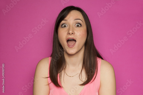 Young surprised woman on pink background