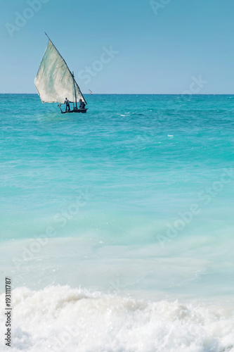 Fotobehang Zanzibar A dhow sailing off into the horizon on a blue sea.