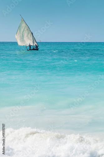 Staande foto Zanzibar A dhow sailing off into the horizon on a blue sea.