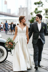 Bride and groom walk  before a white retro car somewhere in New York
