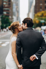 Look from behind at wedding couple kissing on the streets of New York