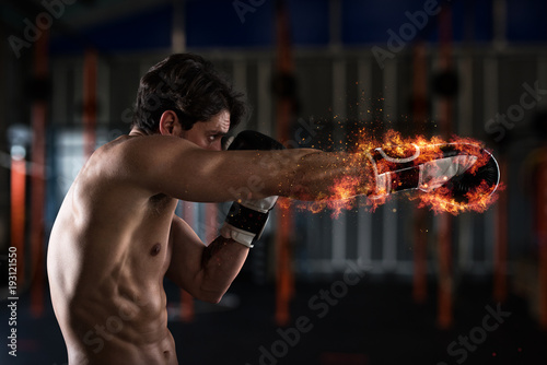 Confident boxer with fiery boxing gloves