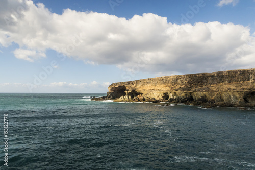 Papiers peints Iles Canaries rugged coastline on Fuerteventura with turquiose water against partially clouded blue sky