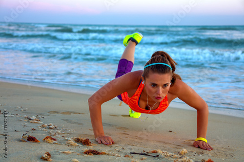 fit woman in sport clothes on seashore at sunset doing pushups