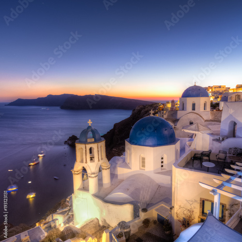 Fotobehang Santorini Cityscape of Oia, traditional greek village with blue domes of churches, Santorini island, Greece at dusk.