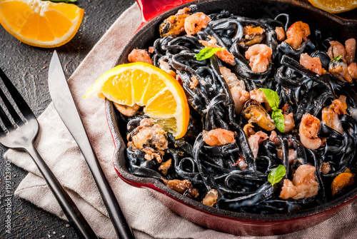 Modern italian dinner, Mediterranean food, black cuttlefish ink spaghetti pasta with seafood, olive oil and basil,  on dark rusty table copy space - 193123900