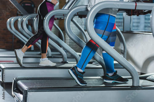 low-section-of-women-training-on-treadmills