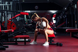 Young woman exercising with weight in the gym.