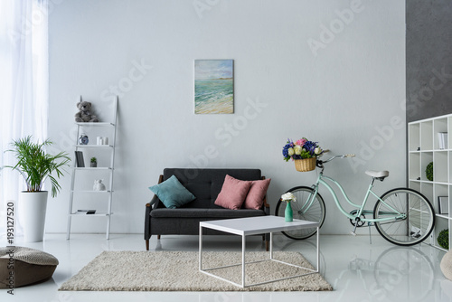 view of stylish living room with retro bicycle, coffee table and sofa