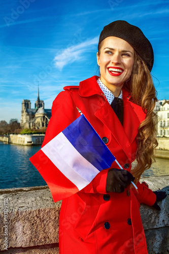 Wall mural smiling woman in Paris with French flag looking into the distance