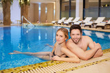 Couple in bathing suits in the pool resting spa center.
