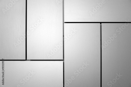 Abstract background created by rectangular panels and lines on the outside of a building. Processed in black and white for effect