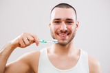 Portrait of young man who is holding toothbrush. - 193143733