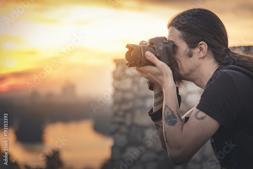 Staande foto Zwavel geel Young photographer with long hair and alternative style taking photographs with his dslr camera, capturing landscape and sunset in a park