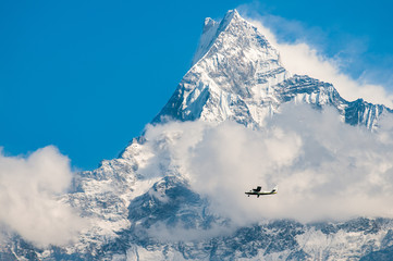 small airplane in front of  the himalayan mountains