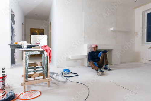 Foto op Plexiglas Wand Handyman is having a rest leaned on a radiator and sitting on the floor with his tools young man