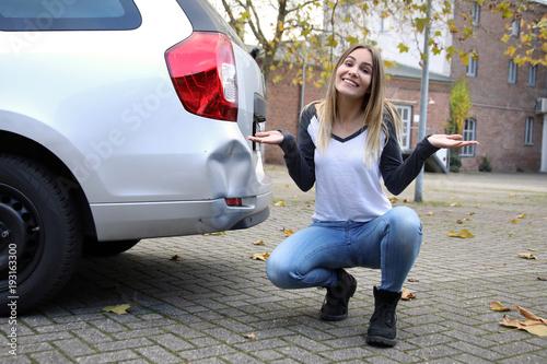 Hübsche blonde Frau sitzt an ihrem Auto mit Unfallschaden und lacht