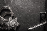 Sheriff star and handcuffs on black slate table closeup. Law concept background - 193167508