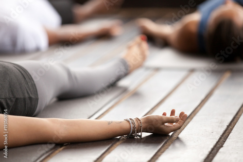 Leinwanddruck Bild Group of young sporty people practicing yoga, lying in Corpse pose, Savasana exercise, working out, resting after practice, female hand with wrist bracelets close up, studio. Healthy lifestyle concept