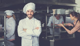 Portrait of satisfied smiling chef on restaurant kitchen - 193172134