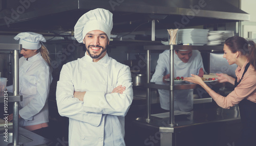 Portrait of satisfied smiling chef on restaurant kitchen