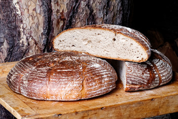 Traditional large farm-style round bread with caraway on wood board. Rustic background.