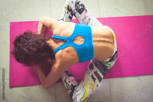 Fototapeta young woman practice yoga indoor shot bend forward in sit position from above