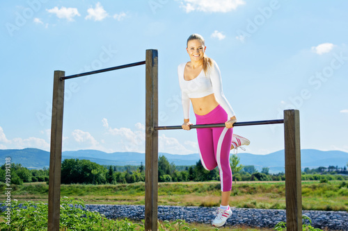Fototapeta Young fitness woman working out outdoors on sunny day with blue sky in the background