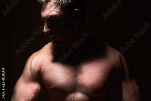 Foto Murales Big and strong muscular man in posing in a low light. Fitness model or a trainer showing his biceps, shoulders and chest. Angry mma fighter or a Bodybuilder is ready to kick ass.