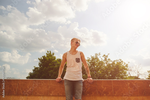 Young man relaxing, enjoying a sunny day while standing on a bui