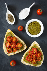 Olive bread roll halves spread with basil pesto and topped with roasted cherry tomato halves, photographed overhead on slate with natural light