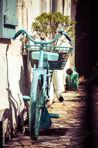 Foto op Plexiglas Fiets very nice vintage bicycle painted blue on the wall of an old house