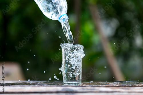 Napój woda nalewa wewnątrz szkło nad światłem słonecznym i naturalnym zielonym tłem. Wyboru ostrości zamazany tło.