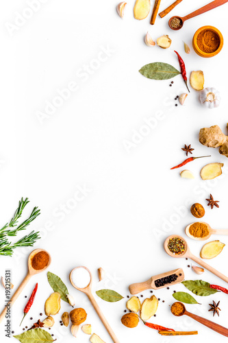 Wall mural Seasoning background. Dry spices near ginger, garlic, rosemary, laurel leaf on white background top view copy space